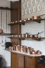 Shiny copper pots, pans and saucepans in white tiled kitchen