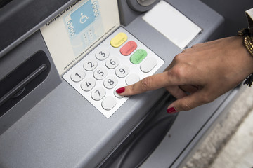 woman with polished nails withdrawing money at atm