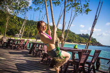 A beautiful girl swings and laughs near beach in cafe. Koh