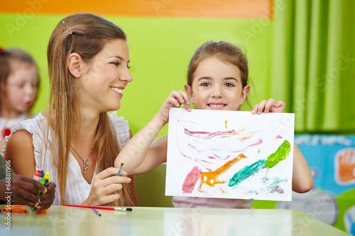 Girl showing self drawn painting in kindergarten