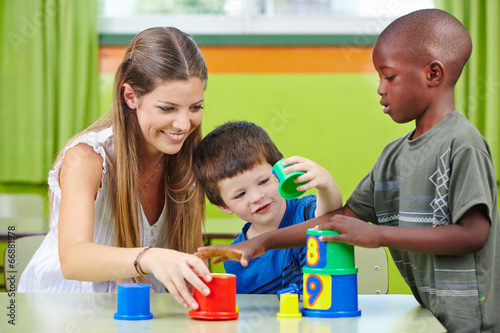 Nursery teacher building tower with children