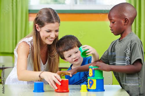 Nursery teacher building tower with children
