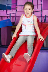 Scared girl on slide in kindergarten