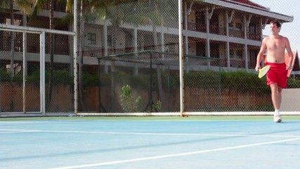 Handosme man with an open-chested playing tennis at the court on