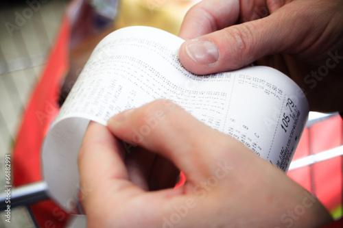 Leinwanddruck Bild Supermarket. paper check receipt bill in hand.