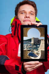 Man showing Dubrovnik in Croatia on tablet. Travel.