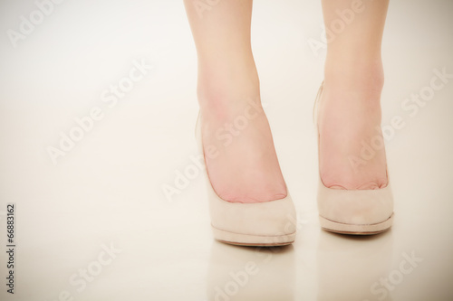 Closeup of female feet in beige high heels.
