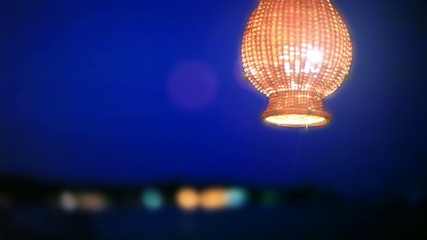 Lantern hanging near beach on blurred night sky background with