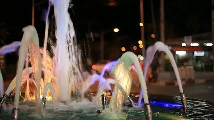 Multicolored fountain illuminated side of the road. Video