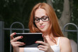 Young redhead woman with a tablet-pc in the park