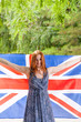 Young beautiful girl against green holds britain flag