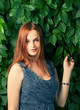 Young pretty red haired women standing against ivy wall