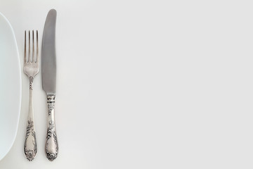 Vintage fork and knife near the plate. Overhead view.
