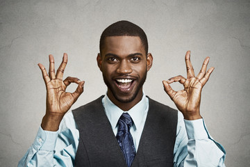 Portrait Business man giving ok sign, grey wall background