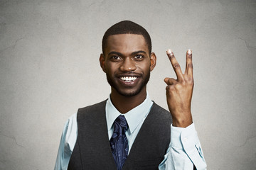 Businessman giving victory two fingers sign grey wall background