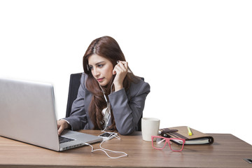 Brunette businesswoman with listening music on the desk