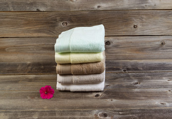 Clean Towels and single pink flower on Weathered Wood