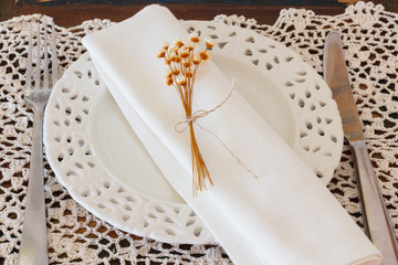 White plate serviette fork knife dried flowers crochet