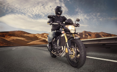 Man seat on the motorcycle on the desert road
