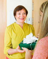Smiling mature neighbor presenting gift to  girl