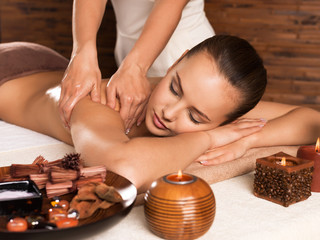 Masseur doing massage on woman body in the spa salon.
