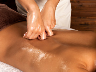 Цoman's body with back massage in spa salon.