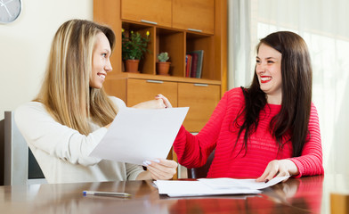 Happy women looking financial documents