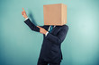 Businessman with box on head is pointing