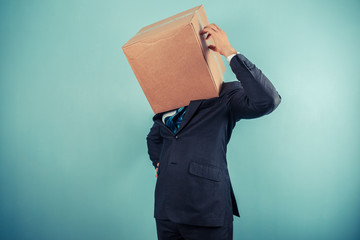 Businessman with box on head is confused