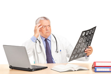 Shocked doctor looking at an x-ray seated at a table