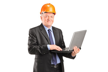 Mature architect with helmet working on a laptop