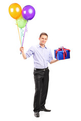 Cheerful man holding balloons and a present