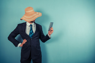 Businessman with beach hat reading on tablet