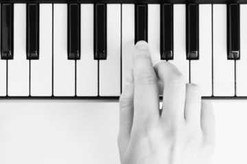 Hand playing on piano