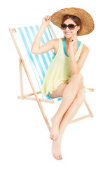 young fashion woman smiling and sitting on a beach chair
