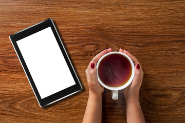woman holding cup of tea with tablet pc on wood
