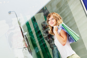 Woman standing near a shop window with shopping bags.