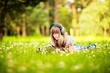 Young woman reading on nature, listening music