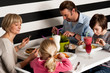 Family of four having meal in restaurant