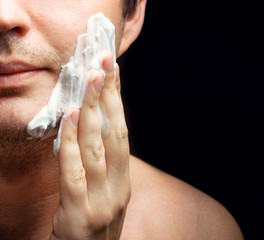 Young man applying a shaving foam