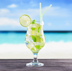 Glass of mojito cocktail on a beach