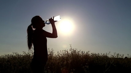 Young woman drink water at sunset.