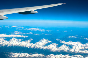 Snow-capped mountains under plane wing