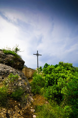 Silhouette image of the cross on the cliff Montserrat mountain