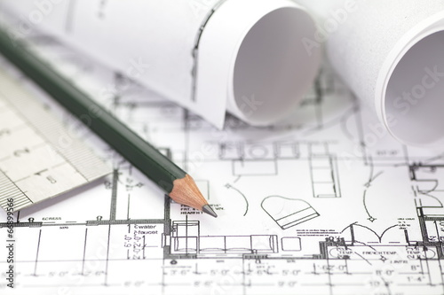 Architect rolls and plans construction project drawing - 66899566
