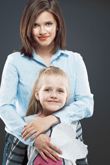 Young business woman with child girl standing against gray