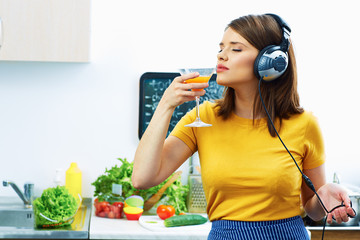 Woman cooking with fun. Girl drinking juice in kitchen