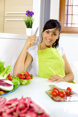 Happy young woman in the kitchen ready to cut tomatoes