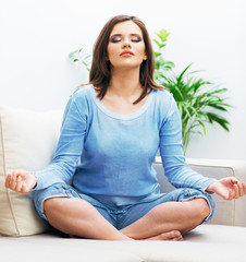 Woman sitting on sofa in yoga pose.