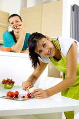 Two women in the kitchen cooking and eating happy